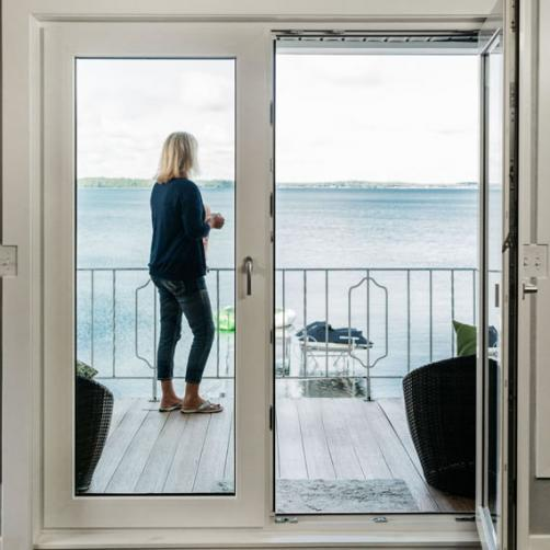 Woman Seen Through a Glass Door Standing on a Balcony | Home Improvement Company
