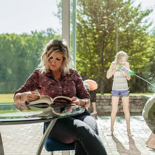 A Woman Reading Indoors and a Child Playing With a Water Gun Outside | Swing Patio Doors